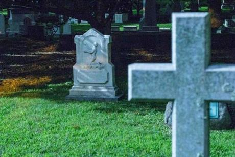 The memorial for Peter Byus (left), an escaped slave from Virginia who worked as a tailor on Beacon Hill, glows in the moonlight.